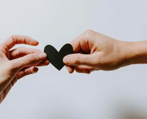 Hände reichen sich Herz